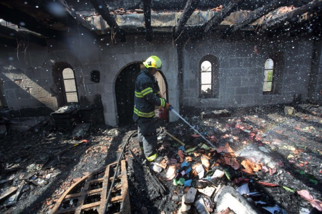 A fireman sprays water on debris at a room located on the complex of the Church of the Multiplication at Tabgha, on the shores on the Sea of Galilee in northern Israel, on June 18, 2015, in the aftermath of a suspected arson attack. The suspected attack totally destroyed an external atrium of the Christian shrine, which is believed by many Christians to be the place where Jesus fed the 5,000 in the miracle of the five loaves and two fish, with a church adviser pointing the finger at Jewish extremists. AFP PHOTO / MENAHEM KAHANAMENAHEM KAHANA/AFP/Getty Images