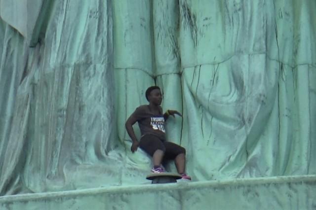 woman-scaling-statue-liberty-july-41